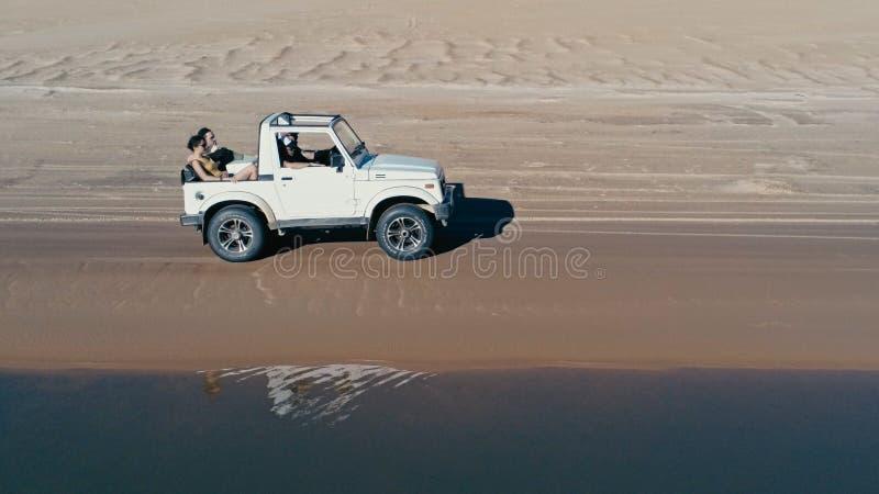 Luftbild einer schönen blauen Lagune nahe bei den WüstenSanddünen mit einem 4x4, das Seitenschuß sich nähert lizenzfreie stockfotografie