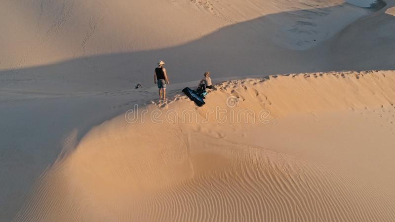 Luftbild von den jungen Leuten, die auf der Spitze einer Sanddüne in der schönen Wüstenumgebung sich vorbereitet für Sandeinstieg stockfotos
