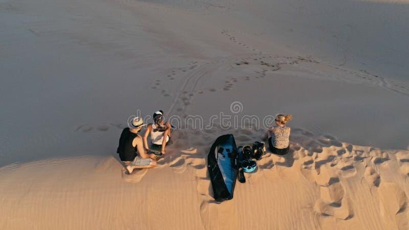 Luftbild von den jungen Leuten, die auf der Spitze einer Sanddüne in der schönen Wüstenumgebung sich vorbereitet für Sandeinstieg stockfoto