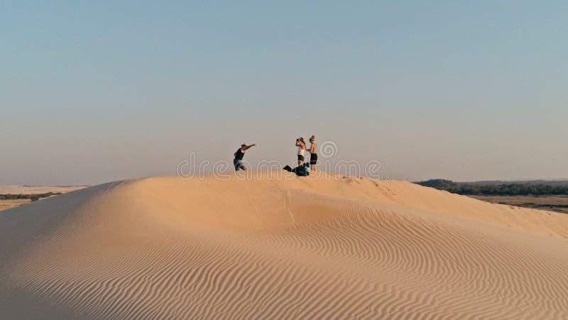 Luftbild von den jungen Leuten, die auf der Spitze einer Sanddüne in der schönen Wüstenumgebung sich vorbereitet für Sandeinstieg lizenzfreie stockfotografie