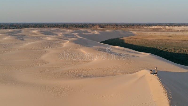 Luftbild von den jungen Leuten, die auf der Spitze einer Sanddüne in der schönen Wüstenumgebung stehen stockfoto