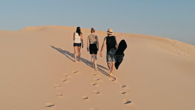 Luftbild von den jungen Leuten, die oben auf eine Sanddüne zur Spitze in einer schönen Wüstenumgebung gehen stockfotos