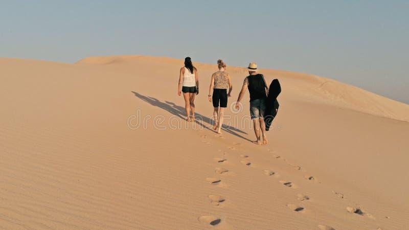 Luftbild von den jungen Leuten, die oben auf eine Sanddüne zur Spitze in einer schönen Wüstenumgebung gehen stockfoto