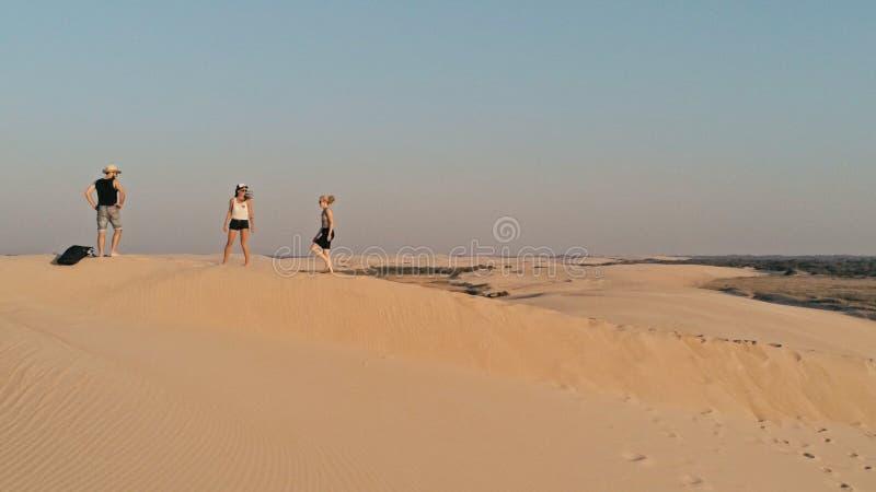 Luftbild von den jungen Leuten, die am Rand einer Sanddüne in der schönen Wüstenumgebung gehen stockfoto