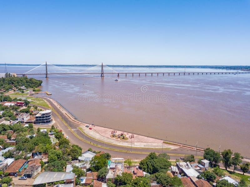 Luftbildfotografie von Encarnacion in Paraguay, welches die Brücke zu den Posadas in Argentinien übersieht lizenzfreie stockbilder