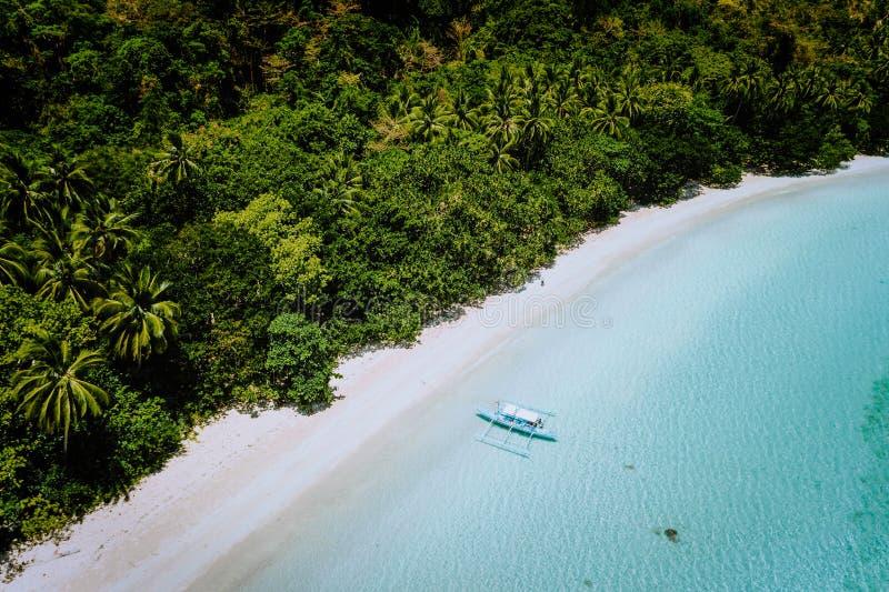 Luftbrummenansicht eines schönen abgelegenen verlassenen tropischen Strandes Einsames Boot in der Türkislagune vor stockfotos