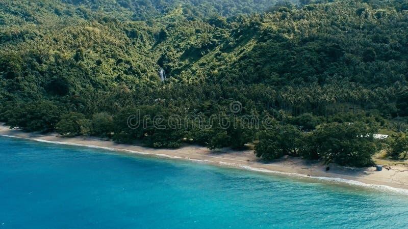 Luftbrummenbild eines South- Pacificdorfs auf einer Ferninsel mit Ufer des sandigen Strandes und üppigem tropischem Regenwalddsch lizenzfreie stockfotografie