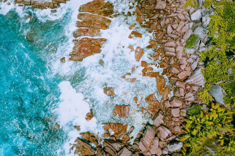 Luftbrummenfoto von Strand Seychellen tropischen Anse-Cocos in La Digue-Insel Weiße rollende Wellen spritzen Granit stockfotos