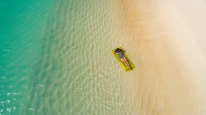 Luftbrummenvogelperspektive des schönen Mädchens, das Spaß auf dem sonnigen tropischen Strand hat seychellen lizenzfreie stockfotografie