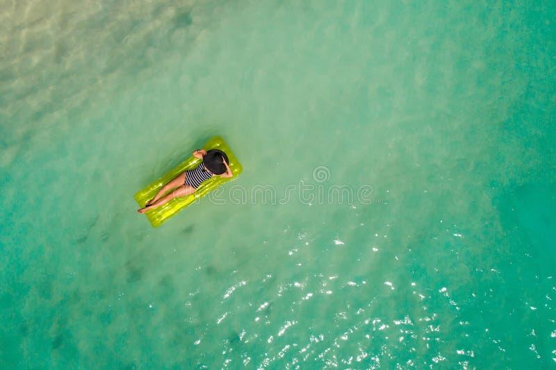Luftbrummenvogelperspektive des schönen Mädchens, das Spaß auf dem sonnigen tropischen Strand hat seychellen lizenzfreie stockfotos