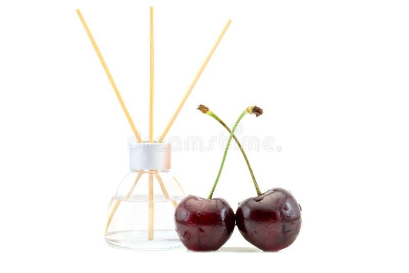 Lufterfrischer mit Kirsche riechen in einem schönen Glasgefäß mit den Stöcken, die auf einem Weiß lokalisiert werden lizenzfreies stockbild
