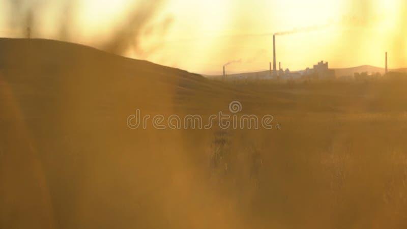 Luftföroreningrök från rör och fabrik med solnedgångbakgrund Industrianläggning i natur på solnedgången arkivfoto