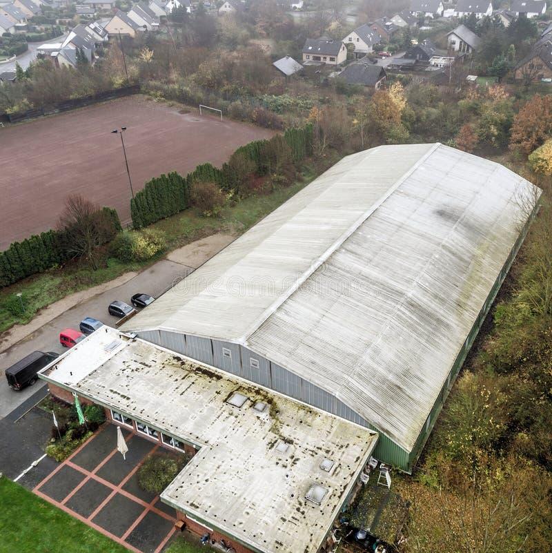 Luftfoto einer alten hässlichen Tennishalle mit einem Wohngebiet stockfoto