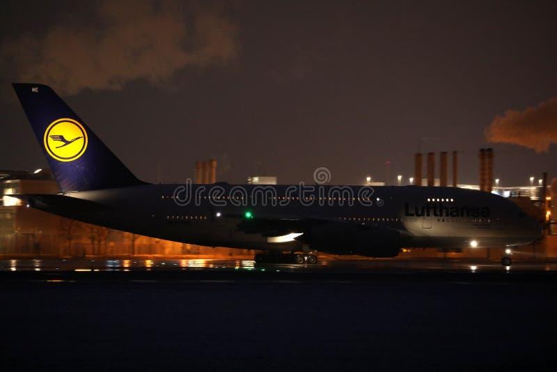 Lufthansa A380 nivå som gör taxien i den Munich flygplatsen, MUC, nattplats arkivfoto