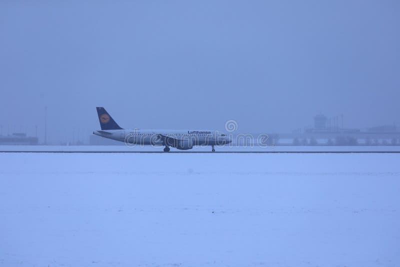 Lufthansa nivå som gör taxien på snö, Munich flygplats MUC royaltyfria foton