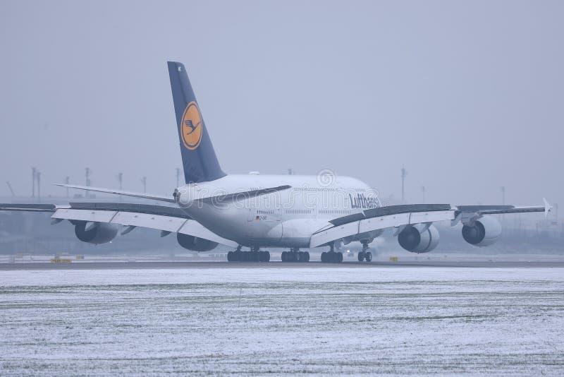 Lufthansa A380 nivå som gör taxien på snö, Munich flygplats MUC royaltyfria foton