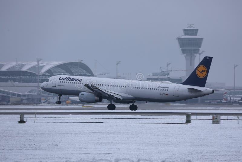 Lufthansa nivå som tar av från den snöig landningsbanan, Munich flygplats MUC arkivfoto