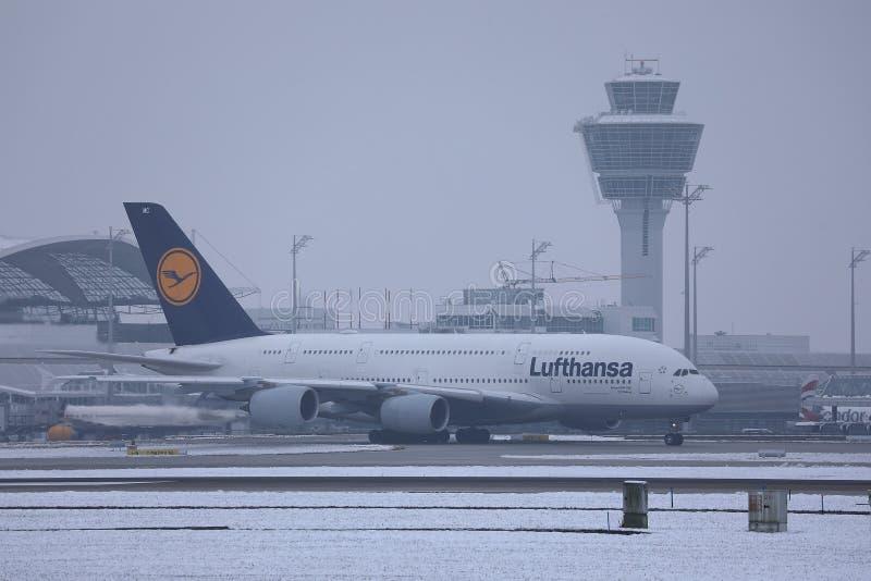 Lufthansa A380 nivå som gör taxien på snö, Munich flygplats MUC royaltyfri bild