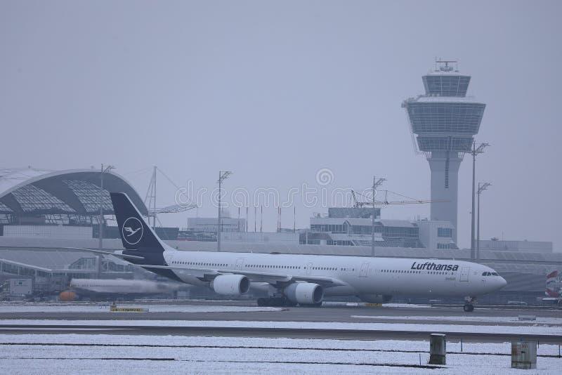 Lufthansa nivå som gör taxien på snö, Munich flygplats MUC royaltyfri fotografi