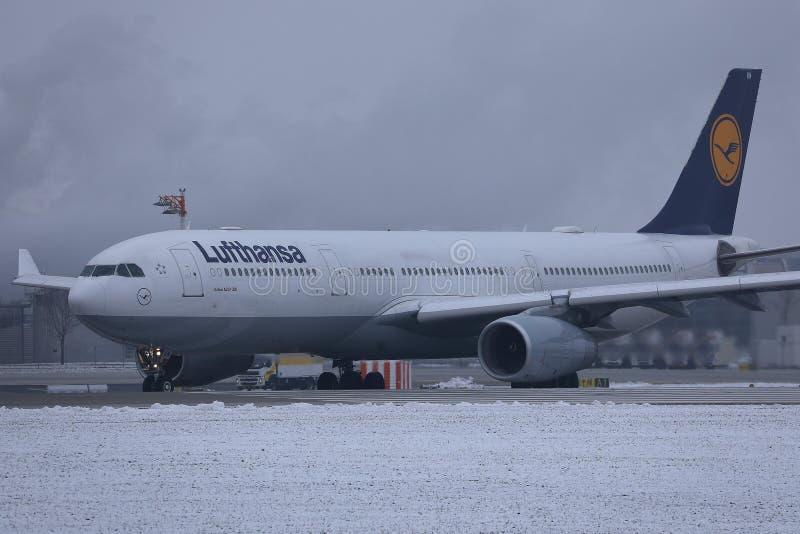 Lufthansa nivå som gör taxien på snö, Munich flygplats MUC arkivfoton