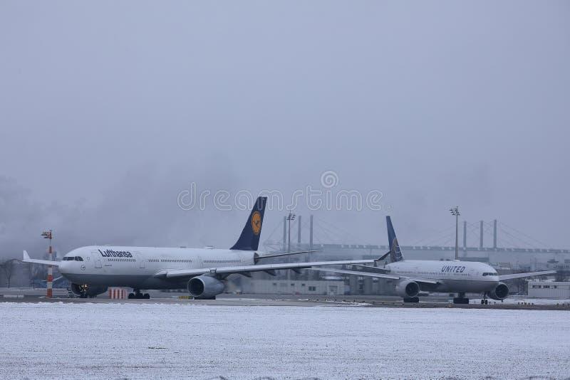 Lufthansa nivå som gör taxien på snö, Munich flygplats MUC royaltyfri bild