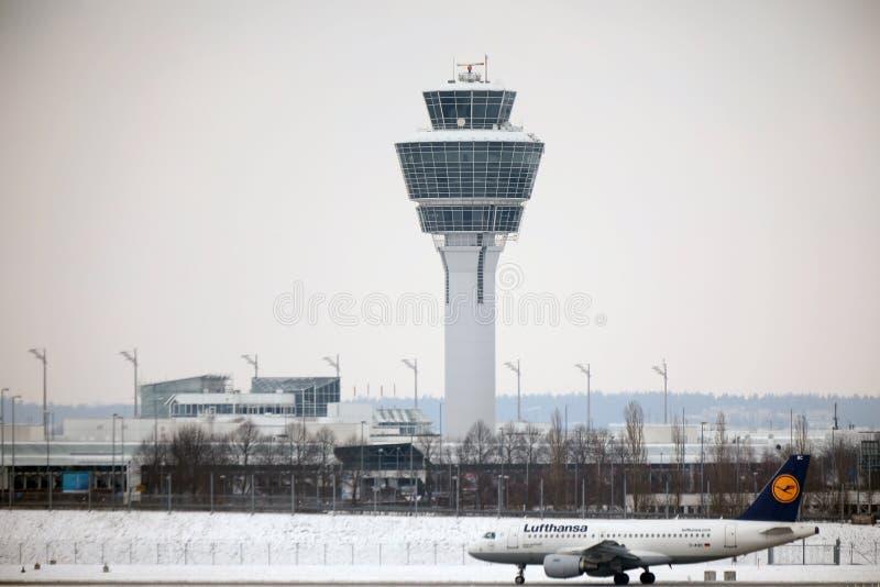 Lufthansa som är plan framme av kontrolltornet i den Munich flygplatsen fotografering för bildbyråer