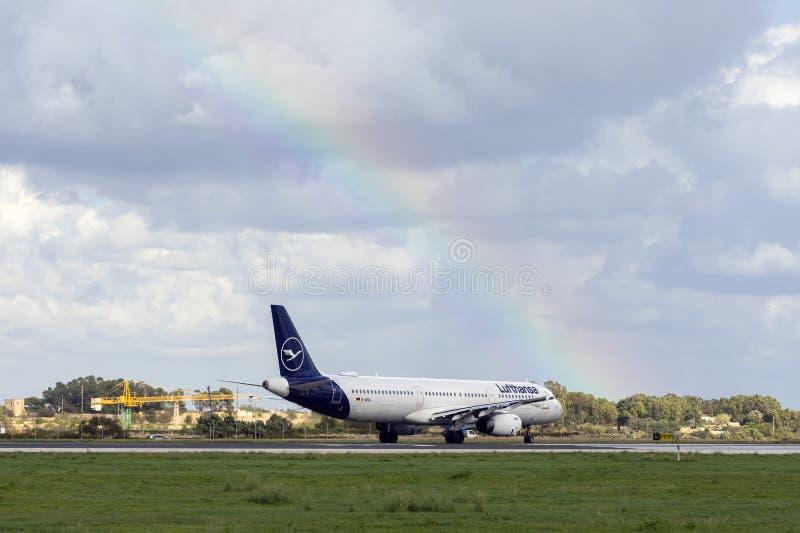 Lufthansa A321 under regnbågen royaltyfri fotografi