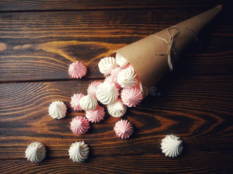 Luftig rosa färg- och vitmaräng på träbakgrund fotografering för bildbyråer