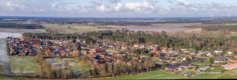 Luftlandschaftsfoto, Panoramablick eines kleinen Dorfs zwischen Feldern und Wiesen, als Fahne für ein Blog oder eine Website stockbild