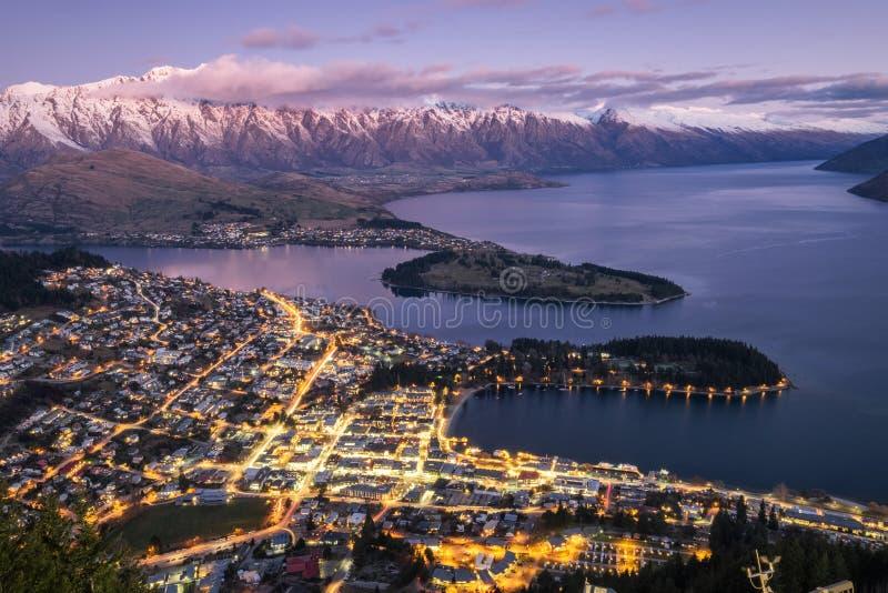 Luftnachtansicht der Dämmerung Queenstown und Schnee bedecktes Remarkables, Neuseeland lizenzfreie stockfotografie