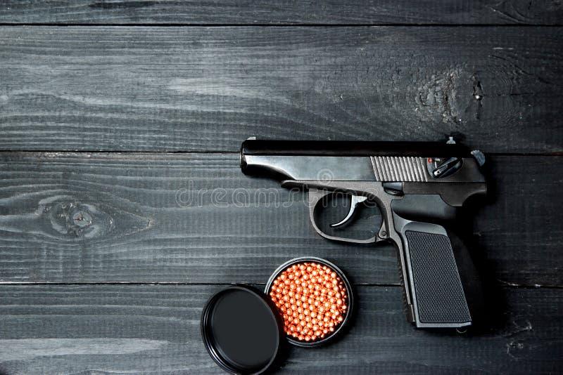 Luftpistol med kulor på en svart träbakgrund arkivfoton
