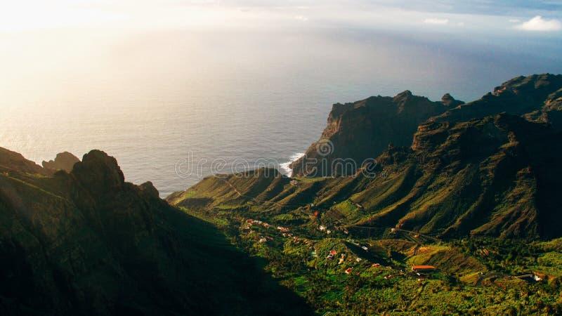 Luftschuß des grünen Berges und der Gebäude auf einem Hügel in der Mitte nahe dem Meer an einem sonnigen Tag stockbilder
