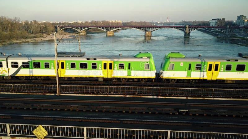 Luftschuß des grünen und gelben Personenzugs, der Eisenbahnbrücke über dem Fluss weitergeht lizenzfreies stockbild