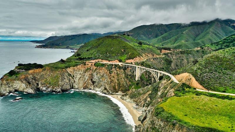 Luftschuß einer schönen Küste der Stadt mit Klippen und grünem Hügel- und bewölktemhimmel lizenzfreie stockbilder