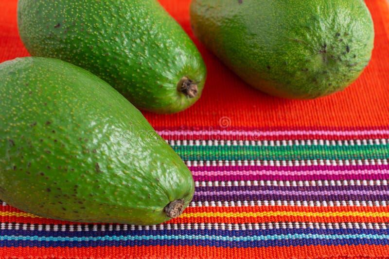 Luftsicht auf drei grüne Avocados, mit selektivem Fokus auf ethnisch roten und farbigen Tischdecken stockfotos