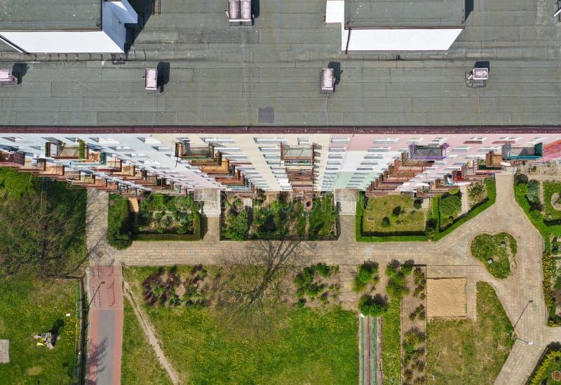 Luftspitze hinunter Ansicht über Dachspitze des flachen Gebäudes des Blockes mit Yard, Pflasterungen, Gärten, mehrfachen Fenstern stockfoto
