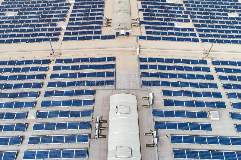 Luftspitze sehen unten auf vielen Sonnenkollektorreihen an, die an vom Fabrikdach ausgerichtet werden lizenzfreies stockfoto