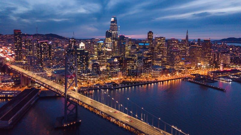 Luftstadtbildansicht von San Francisco und die Bucht-Brücke bei Nig lizenzfreie stockfotos