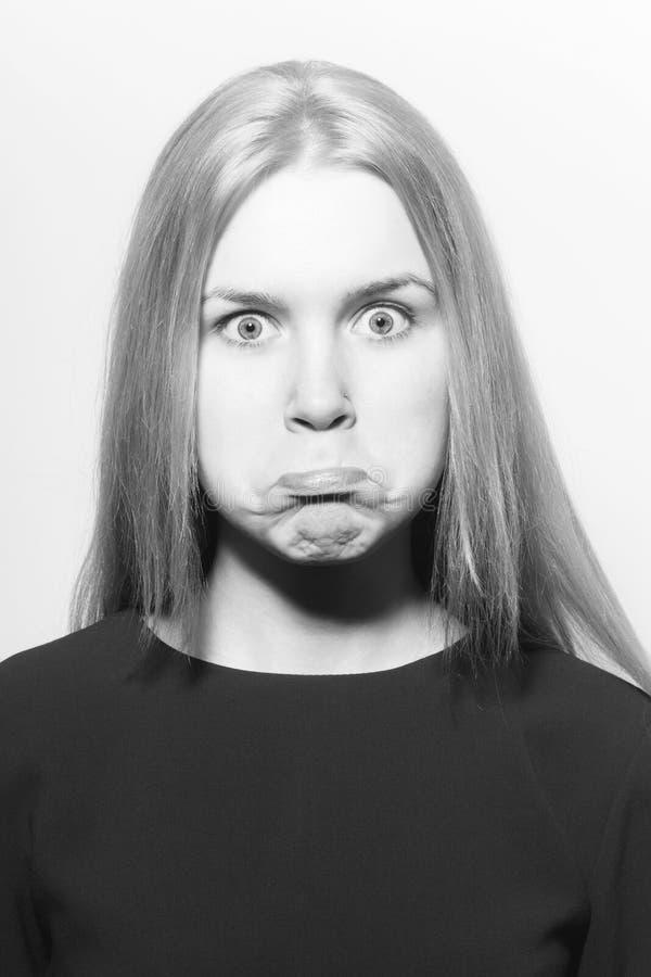 Luftstoßende Backen des Mädchens auf lustigem Gesicht Frau lizenzfreie stockfotografie