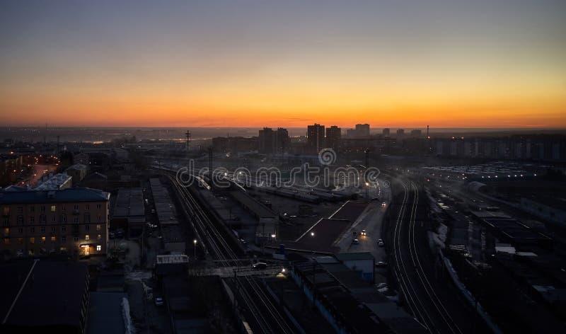Lufttrieb des Sonnenuntergangs über Stadt und großem Bahnhof mit Zügen stockbilder
