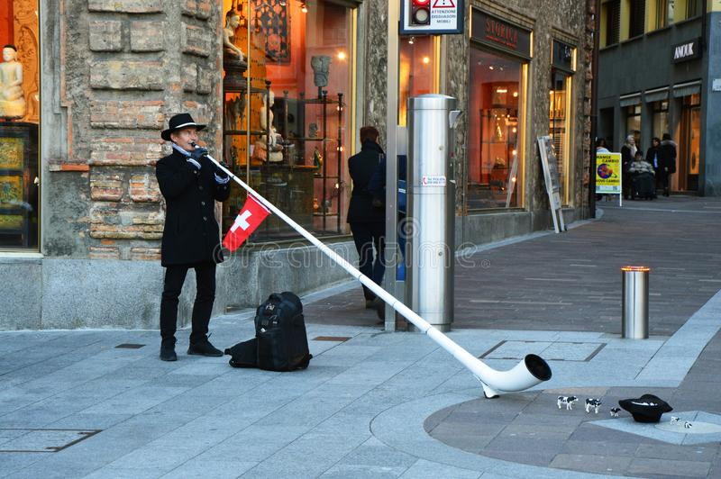 LUGANO SCHWEIZ - NOVEMBER 27, 2017: Schweizisk musiker med en typiska Alphorn i den Lugano staden En man i traditionell schweizar royaltyfria bilder