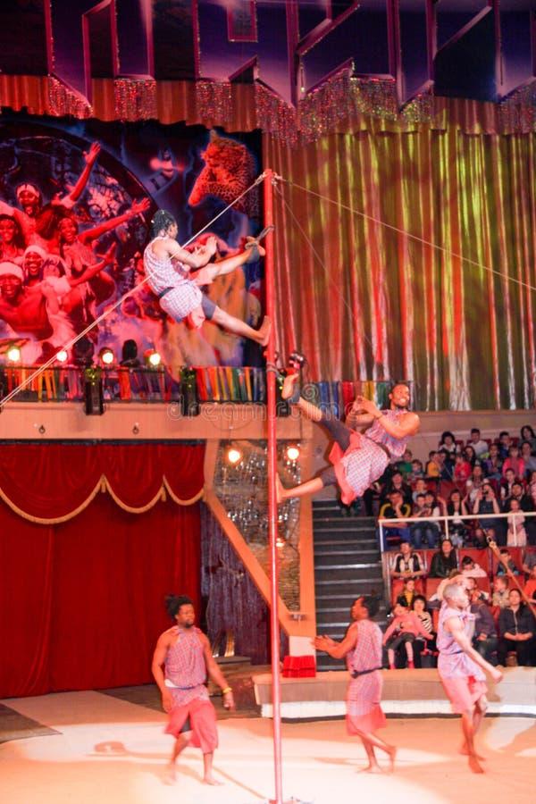 LUGANSK, UKRAINE - 9. APRIL 2016: einige Akrobaten in einer Zirkusleistung auf dem Pfosten stockfotografie