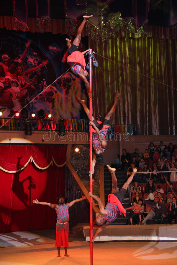 LUGANSK, UKRAINE - 9 AVRIL 2016 : plusieurs acrobates dans une représentation de cirque sur le poteau photo stock