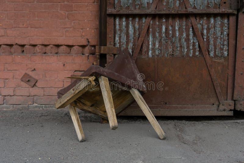 Lugar abandonado Cadeira velha de madeira quebrada na parede de tijolo e no fundo oxidado do metal imagem de stock royalty free