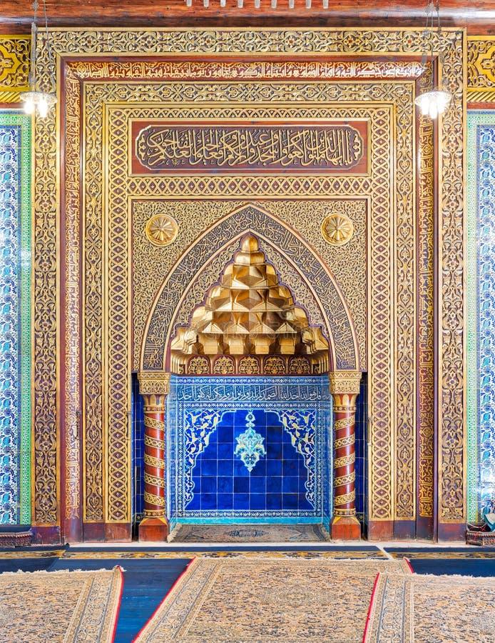 Lugar arqueado adornado de oro del mihrab con el estampado de flores, las baldosas cerámicas turcas azules y la caligrafía árabe, fotografía de archivo libre de regalías