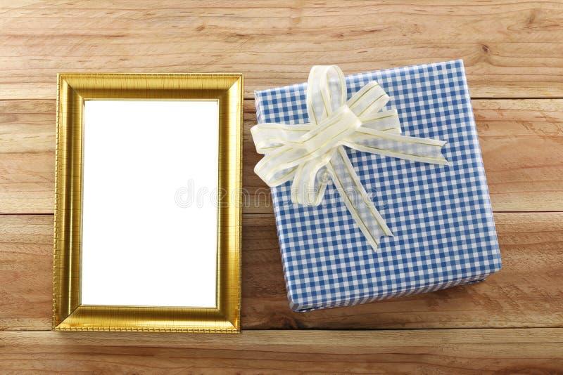 Lugar azul da caixa de presente perto do quadro de madeira do ouro no assoalho de madeira fotografia de stock