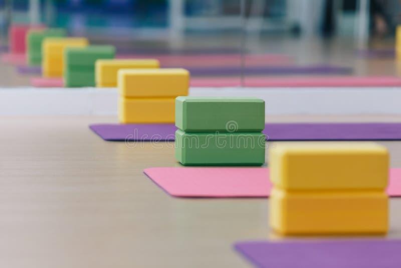 Lugar colorido dos blocos e das esteiras da ioga no assoalho de madeira da textura Apronte para a classe da ioga imagens de stock royalty free
