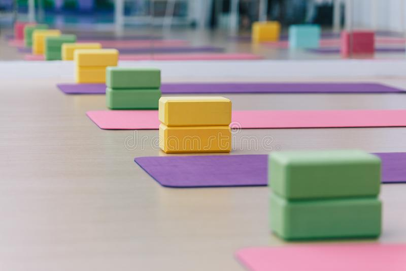 Lugar colorido dos blocos e das esteiras da ioga no assoalho de madeira da textura Apronte para a classe da ioga fotografia de stock royalty free
