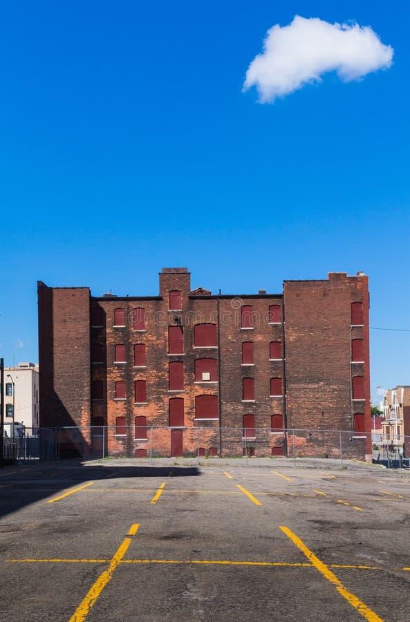 Lugar de estacionamento e construção abandonada fotografia de stock