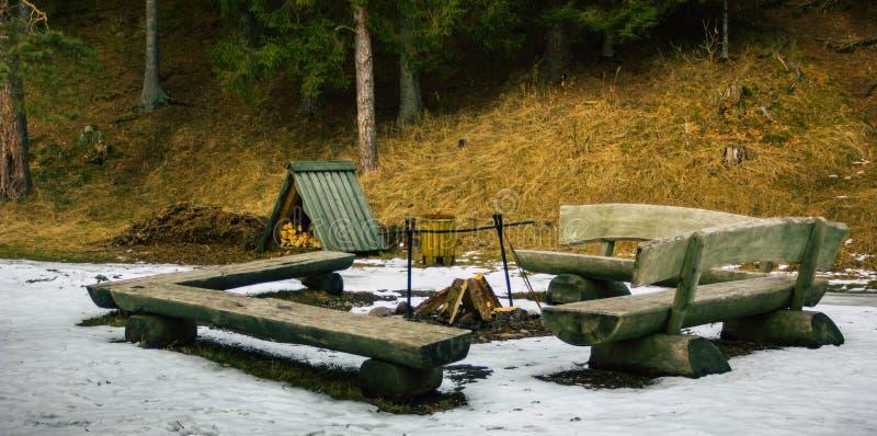 Lugar de la hoguera con una madera en ella Surronded por los bancos en un día de invierno nublado foto de archivo